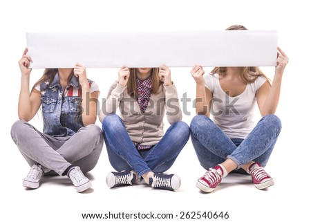 Three girls sitting cross-legged and closed faces white table with empty space for the text. Isolated on white background. - stock photo