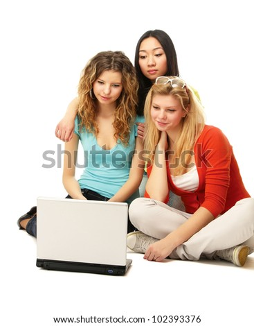 Three girls sitting on the floor with a laptop. isolated on white background