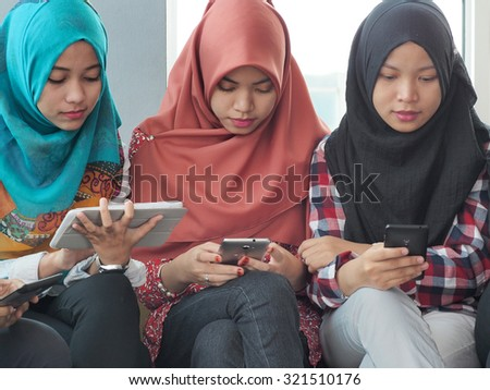 Three girls sitting together while playing their hand phones. - stock photo