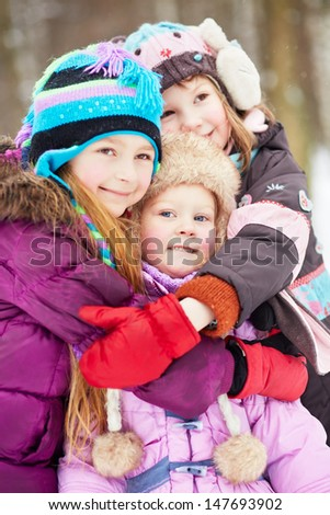 Three girls stand embracing each other in winter park - stock photo