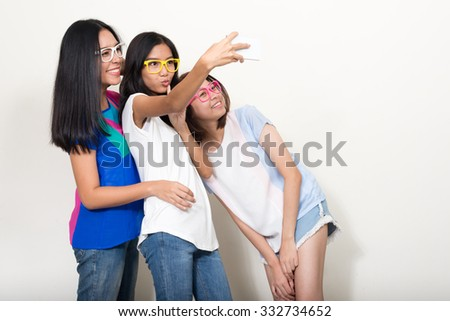 Three girls taking selfie picture with their mobile phone