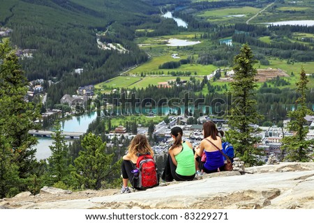 Three girls-tourists sitting on a grief and looking at a panorama of a small town Banff in a Bow river valley (Banff National Park. Alberta. Canada) - stock photo