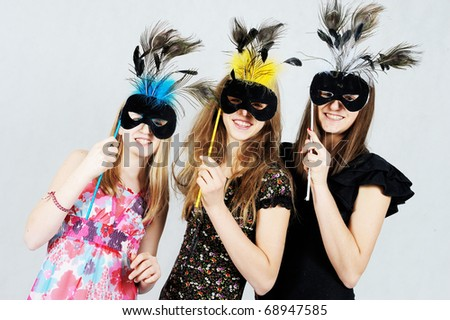 Three girls wearing masks - stock photo