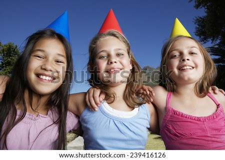 Three Girls Wearing Party Hats Embracing - stock photo