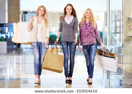 Three girls with shopping bags in store - stock photo