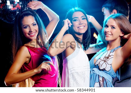 Three glamorous girls enjoying themselves while dancing in night club - stock photo