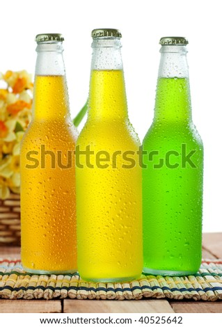 Three glass bottle with cold drinks on wooden table on white background