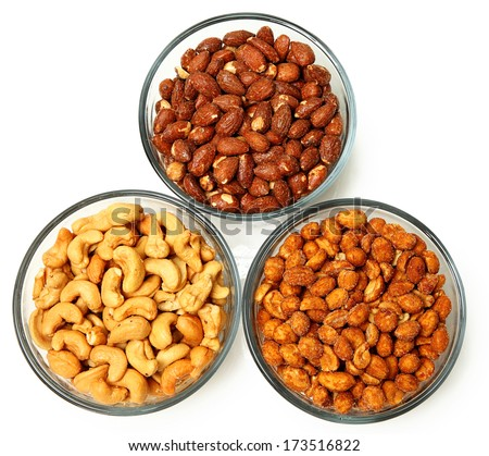 Three glass bowls filled with cashews, salted roasted almonds and honey roasted peanuts. Over white. - stock photo