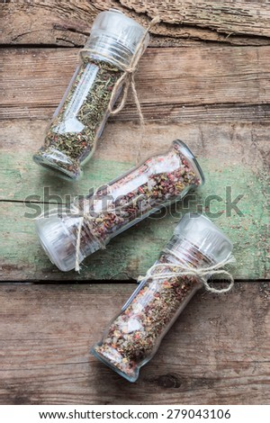 three glass containers with seasonings, spices and herbs - stock photo