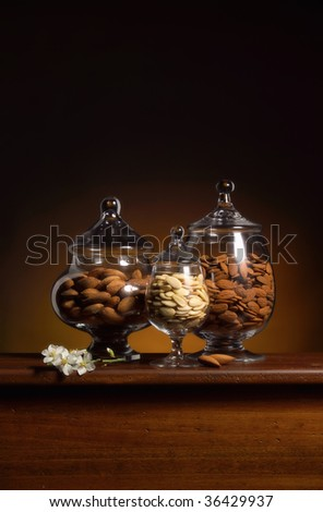 Three glass conteiners with almonds with an almond flower on a table - stock photo