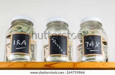 Three glass jars with chalk labels used for saving US dollar bills and notes for IRA, tax and college funds - stock photo