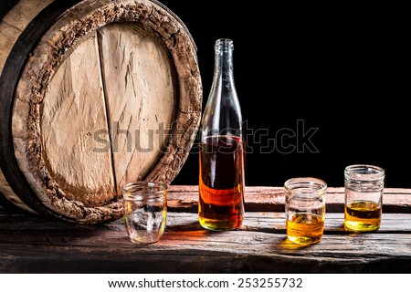 Three glass of aged whisky and bottle - stock photo
