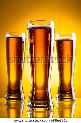 Three glass of beer over yellow background - stock photo