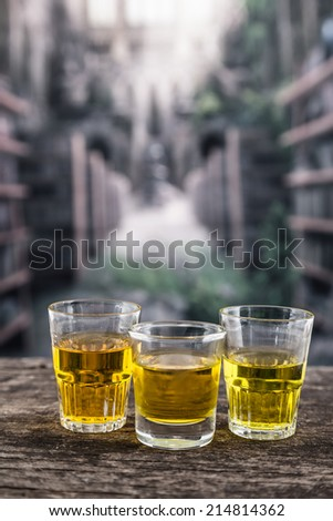Three glass shots with yellow liqour resembling whiskey, rum, tequila, spirit on wooden table - stock photo