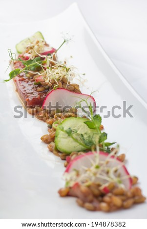 Three glasses filled with appetizers of salmon, salads and a variety of  herbs and flowers