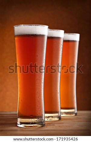 three glasses of beer on a wooden table - stock photo