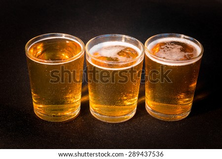 Three glasses of beer seen from above - stock photo