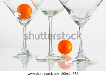 Three glasses of champagne and golf equipments on the glass table - stock photo