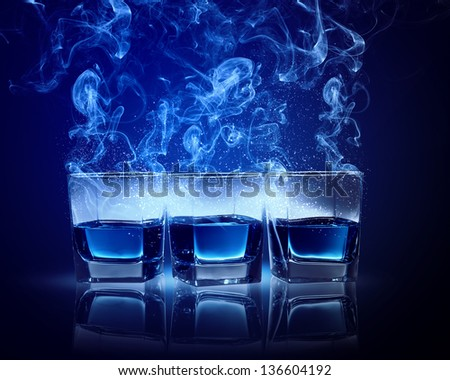 Three glasses of cocktail with fumes and falling snow - stock photo