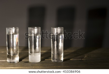 three glasses of cocktails shot on a wooden table - stock photo