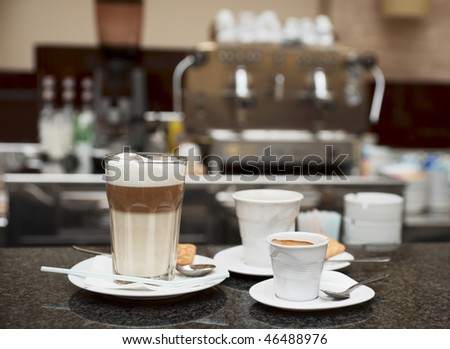 Three glasses of coffee, cafe equipment in blurred backgound - stock photo