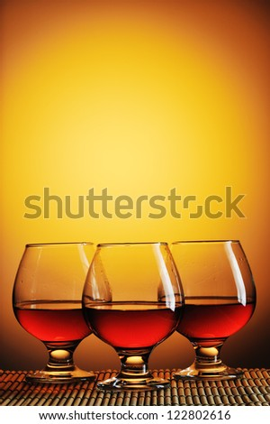 Three glasses of cognac on yellow background - stock photo
