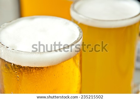 Three glasses of fresh and foamy beer just served - stock photo