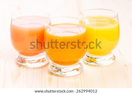 Three glasses of fresh natural juices. Grapefruit, orange and apple and carrot juice on wooden background.  - stock photo