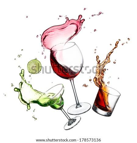 three glasses of splashing red wine, cocktail and whiskey - stock photo