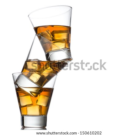 Three glasses of whiskey on the rocks, one on top of the other isolated on white  - stock photo