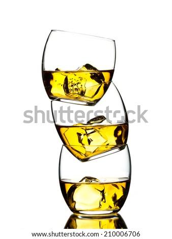 Three glasses of whiskey on white background - stock photo