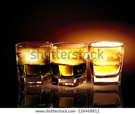 Three glasses of whiskey with nature illustration in - stock photo