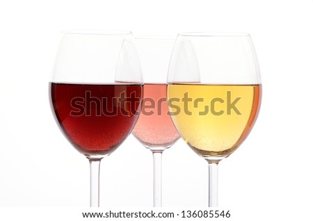 Three glasses of wine on a white background with selective focus on the foreground