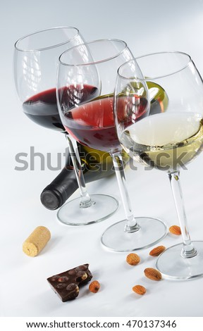 Three glasses of wine, white, pink and red on a light background