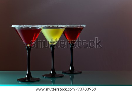 Three glasses with a cocktail on a dark background. - stock photo