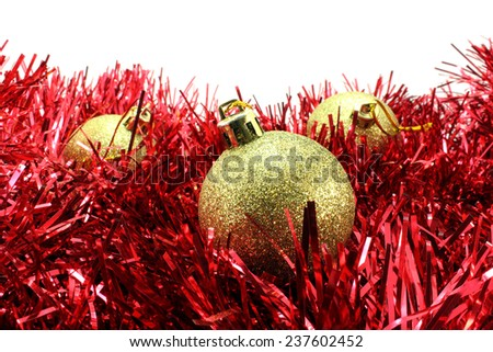 Three gold Christmas ball with sparkles on the red tinsel - stock photo