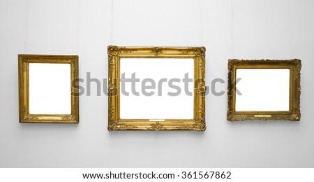 Three gold empty frame on white wall - stock photo