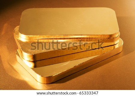 three gold ingots on a golden background. shallow depth of field. - stock photo