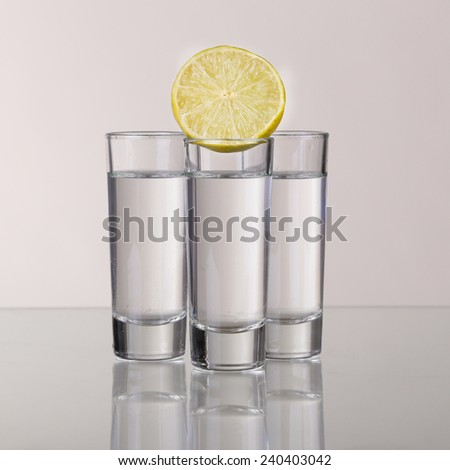 Three gold tequila shots with lime isolated on white background