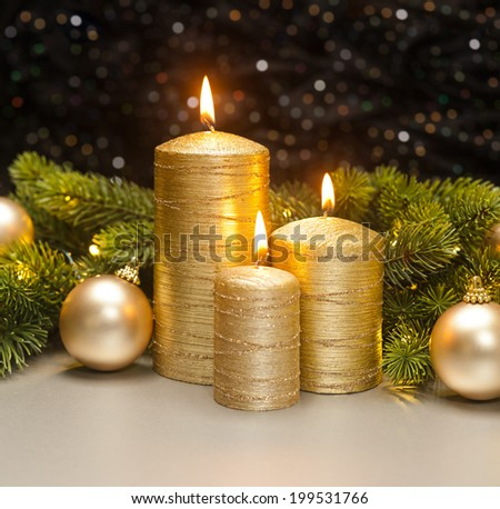 Three golden Candles with Christmas tree branches decorated - stock photo