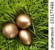 Three golden eggs are in the green grass, close up - stock photo