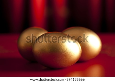 Three golden eggs on red curtain background - stock photo