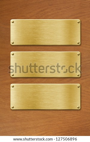 three golden metal plates over wood texture