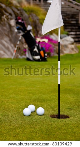 Three golf balls on green with flag. Shallow depth of field. Focus on the closest balls and the hole. - stock photo