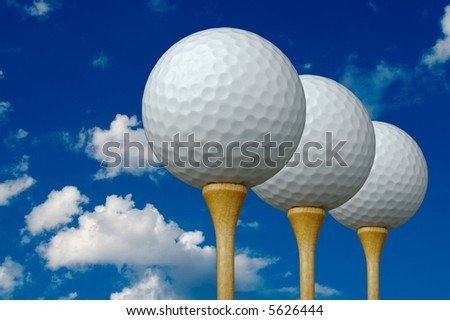 Three Golf Balls & Tees on the right with clouds and sky background. - stock photo