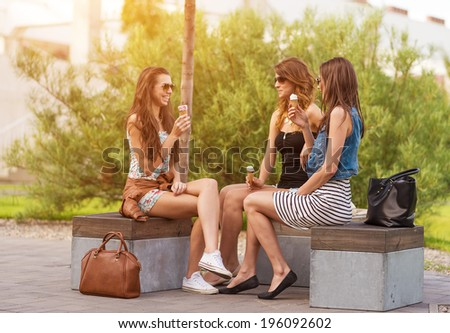 Three good girlfriends eat ice cream on a bench in the City - stock photo