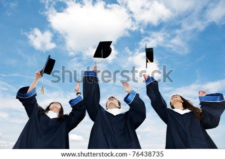 three graduate students tossing up hats over blue sky - stock photo