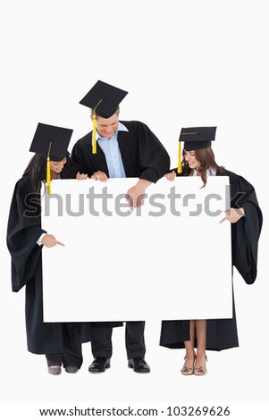 Three graduates point to a spot on the blank sign which will be filled by information - stock photo