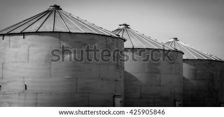 Three grain silos leading off into the distance in black & white - stock photo