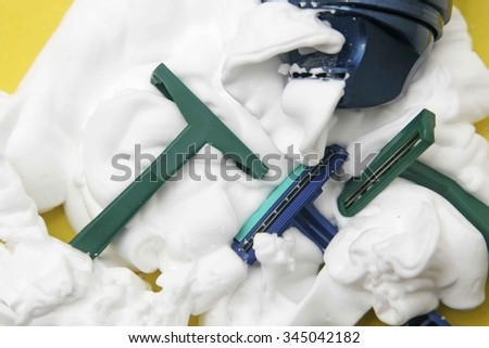 Three green and blue plastic shaving disposable man's razors on yellow background of shaving gel or white foam. - stock photo